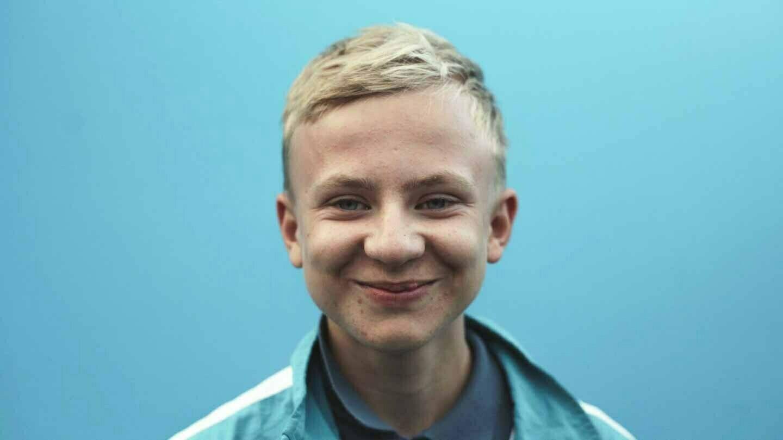 Elias, grinsend, im Portrait vor blauen Hintergrund