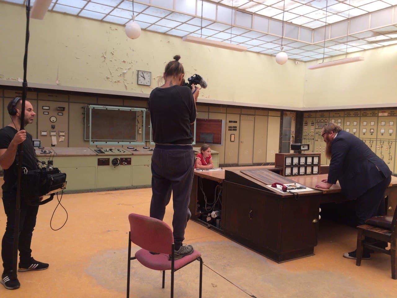 Doro sitzt am Kontrolltisch eines Kraftwerks und wird von drei Erwachsenen gefilmt.