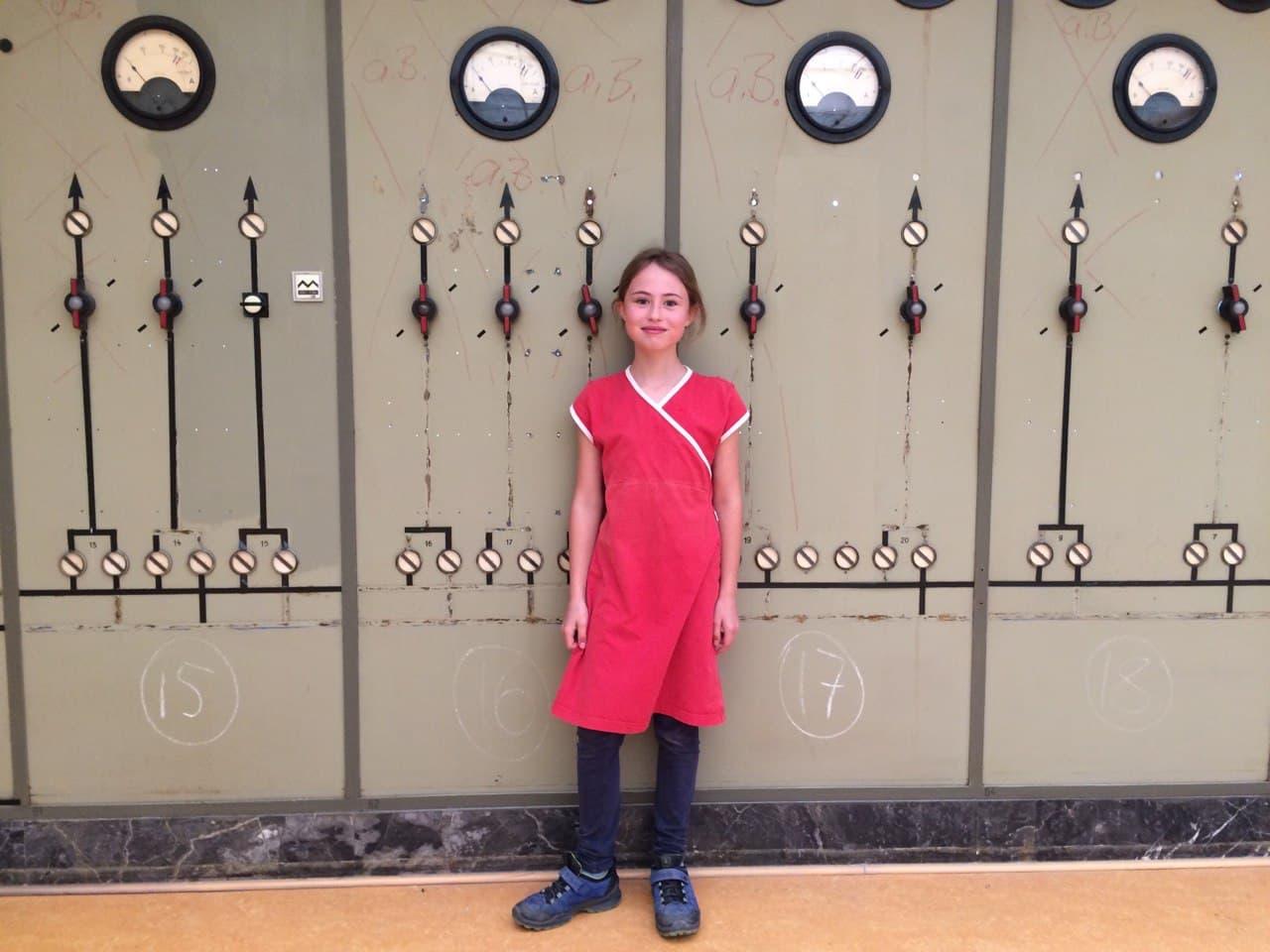Doro steht vor verschiedenen Kontrollgeräten. Sie trägt ein rotes Kleid, eine blaue Hose und dunkle Turnschuhe.