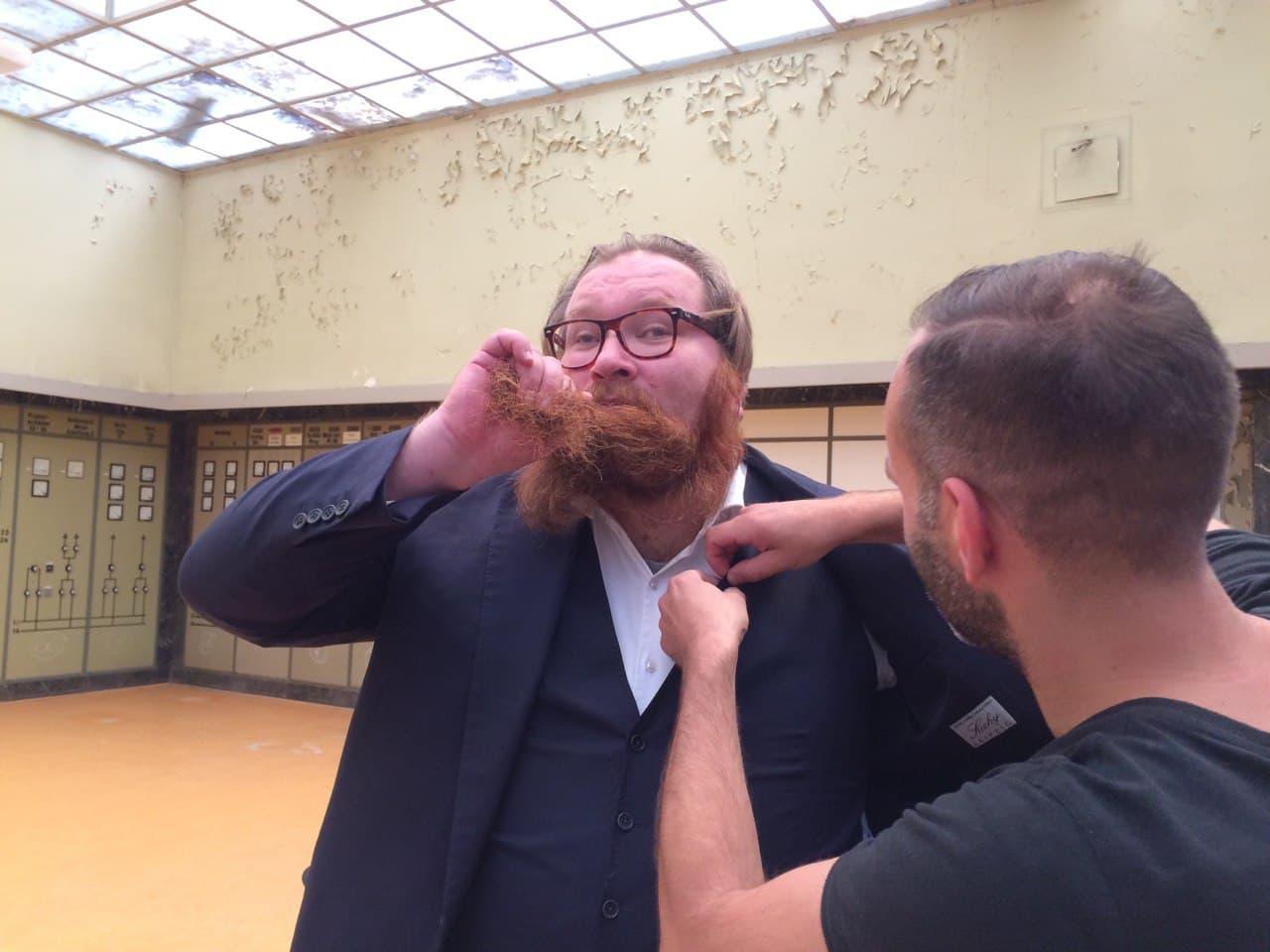 Ein Mann mit einem langen, roten Bart wird gerade zurechtgemacht