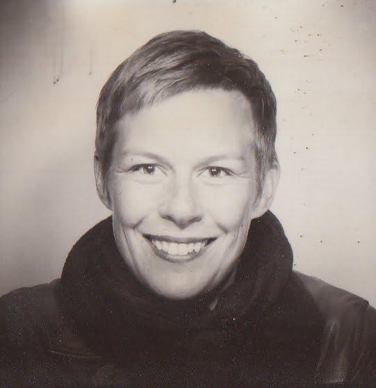 Luc Carolin Ziemann im Portät. Das Bild ist im Stil eines Fotoautomaten in Schwarz und Weiss. Luc trägt kurze, helle Haare, einen dicken Schaal und ein dunkles Oberteil. Sie grinst freundlich in die Kamera.