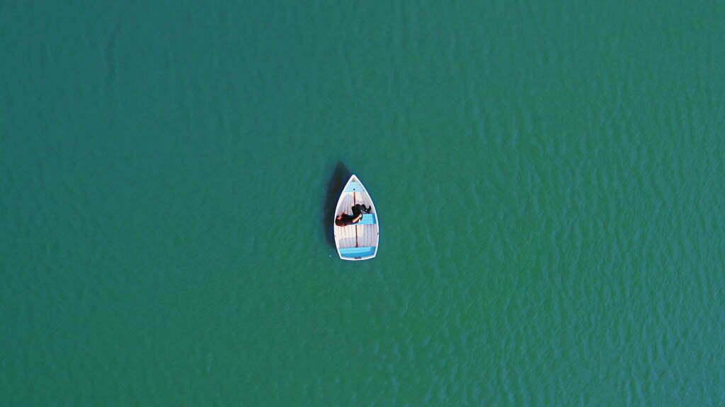 Aus der Vogelperspektive sieht man Roya in einem kleinen Ruderboot mitten in einem Gewässer liegen.