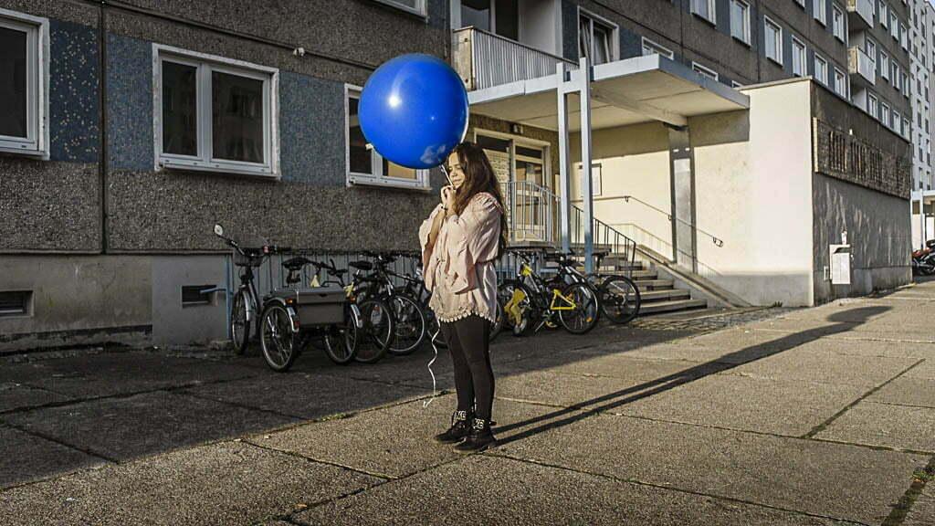 Roya hält einen blauen Ballon während sie vor einem Wohnhaus steht