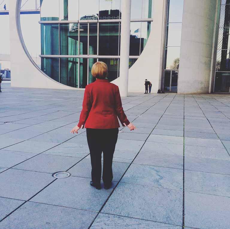 Eine Merkel-Doppelgängerin steht vor dem Bundeskanzleramt